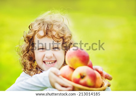 Happy girl holding a basket of apples. - stock photo