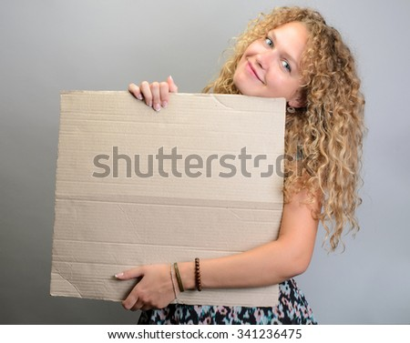 Happy girl holding blank board smiling on grey background