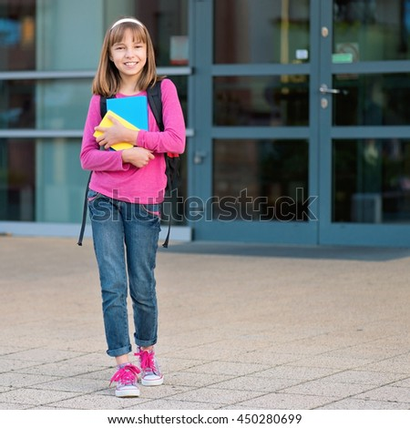 Happy girl holding books in school yard. Full length outdoor portrait.