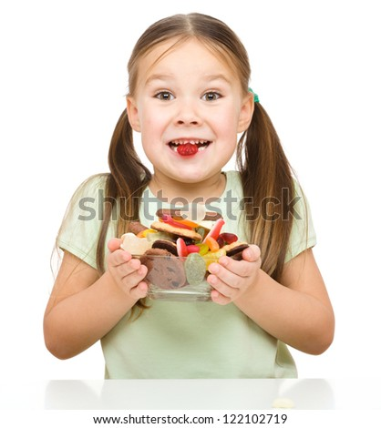 Happy girl holding bowl full of candies and one in her mouth, isolated over white - stock photo