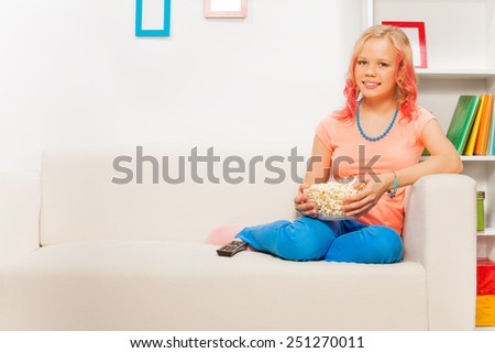 Happy girl holding bowl with popcorn on white sofa - stock photo