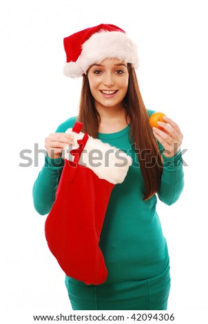 Happy girl holding christmas stocking and clementine on white background - stock photo