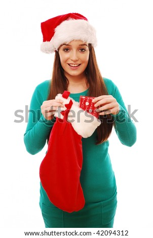 Happy girl holding christmas stocking and present on white background - stock photo