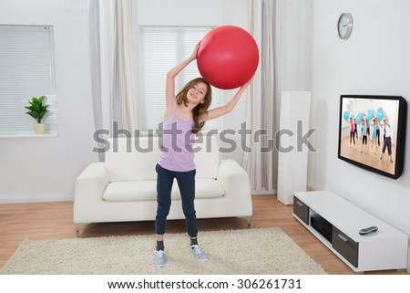Happy Girl Holding Fitness Ball In Front Of Television At Home - stock photo