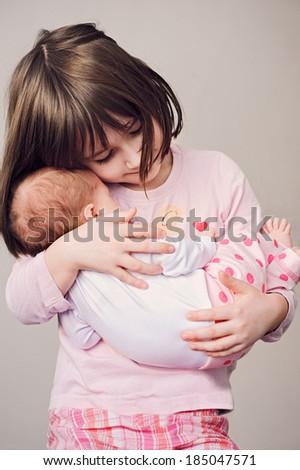 Happy girl holding her newborn sister - stock photo