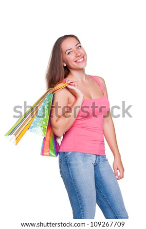 happy girl holding shopping bags and smiling over white background - stock photo