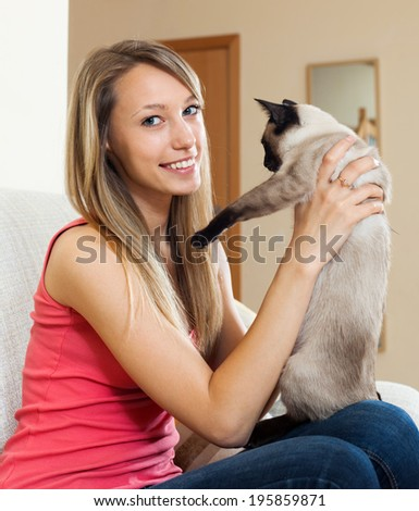 Happy girl holding Siamese kitten in arms and smiling