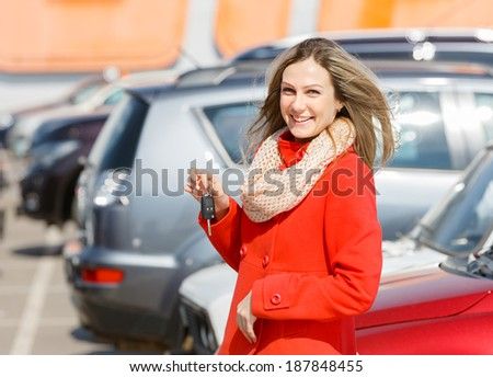 happy girl holding the keys in hand over cars