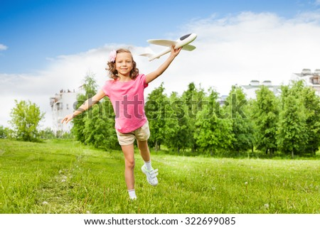 Happy girl holds airplane toy with one leg up