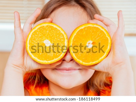 Happy girl holds half of orange near the face