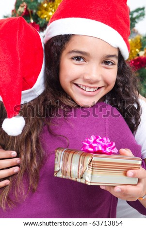 happy girl hugging mother after receiving her Christmas gift - stock photo