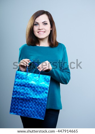 happy girl in a blue t-shirt with a shopping bag in hand .On a gray background - stock photo