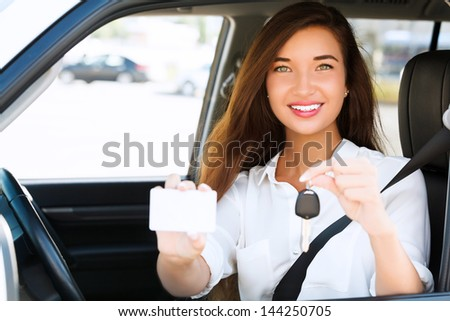 Happy girl in a car showing a key and an empty white card for your message - stock photo