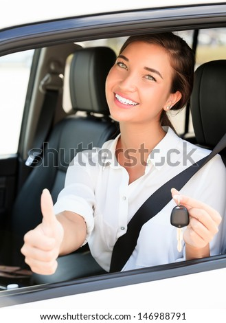 Happy girl in a car showing a key and thumb up gesture  - stock photo