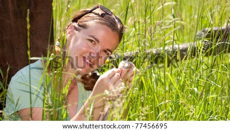 happy girl in a grass touching a daisy