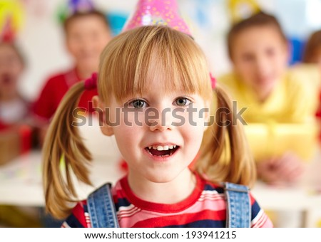 Happy girl in birthday cap looking at camera with her friends on background - stock photo