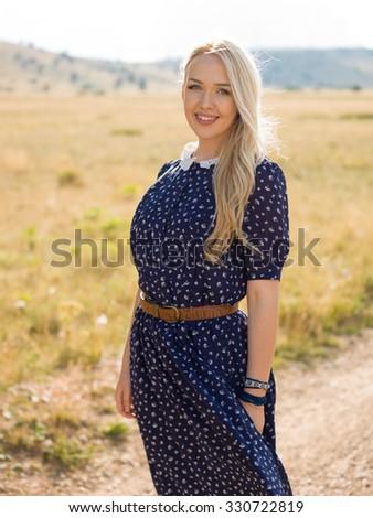 Happy girl in blue dress on wheat field, portrait of attractive  - stock photo