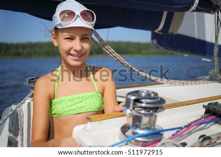 Happy girl in cap on yacht during sailing on river at sunny summer day