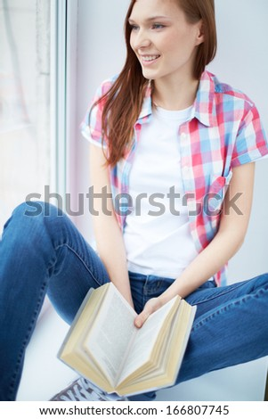 Happy girl in casual clothes looking in the window while reading book