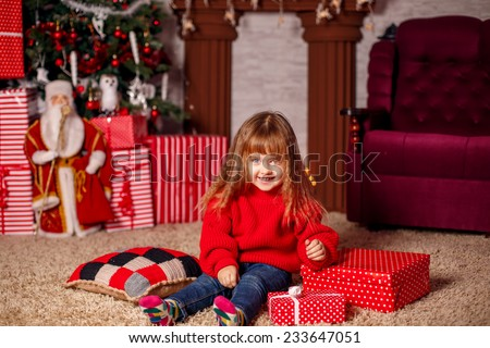 happy girl in Christmas hat near the Christmas tree. Christmas holidays - stock photo