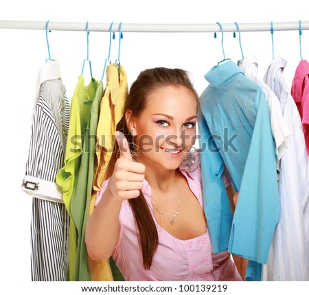 Happy girl in clothing store showing thumbs up isolated - stock photo