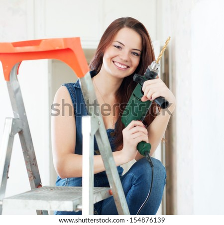 Happy girl in dungarees with drill on stepladder - stock photo