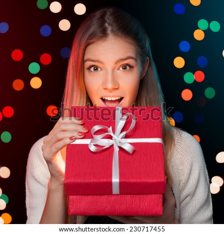 Happy girl in excitement opening Christmas box which is glowing inside. Excited woman. Christmas Gift - stock photo