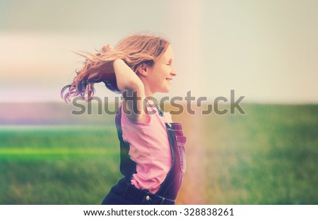 happy girl in field, with creative light leak - stock photo