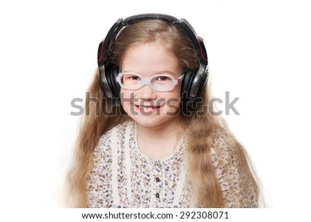 happy girl in glasses and headphones listens to music - stock photo