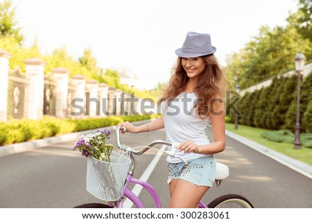happy girl in hat with a bicycle - stock photo