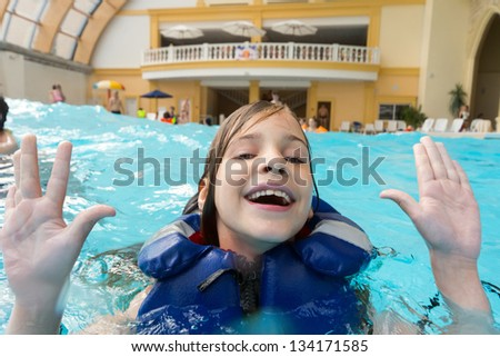 Happy girl in lifejacket in the water park with his hands up. - stock photo