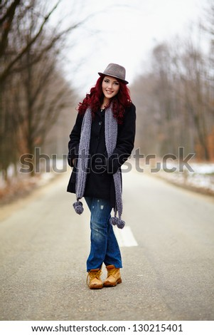 Happy girl in outdoor full length, hands in pockets - stock photo