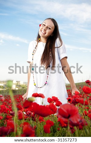Happy girl in poppy flowers - stock photo