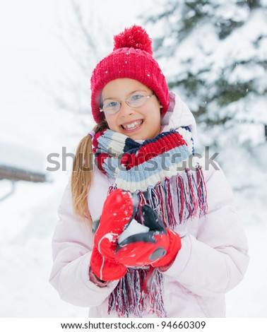 Happy girl in red hat smiling and having fun outdoors on snowing winter day, making snowball and loking at the camera
