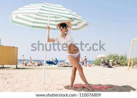 happy girl in retro style by color umbrella on the beach. outdoors