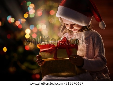 Happy girl in Santa cap looking at wonderful Christmas present in giftbox - stock photo