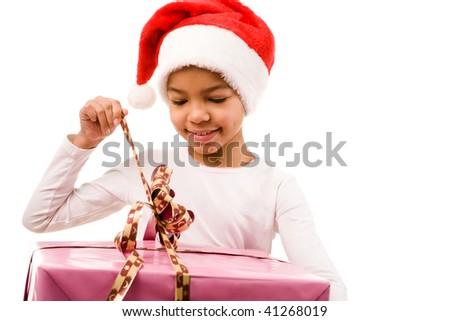 Happy girl in Santa cap unwrapping ribbon of smart present - stock photo