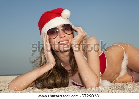 Happy girl in Santa Clause suit having rest on the beach - stock photo