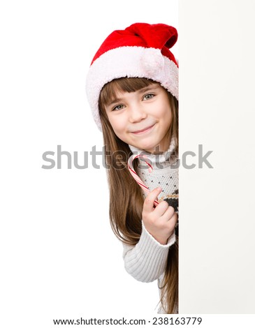 happy girl in santa hat with Christmas candy cane standing behind white board. isolated on white background - stock photo