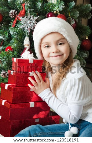 Happy girl in Santa hat with gifts near christmas tree