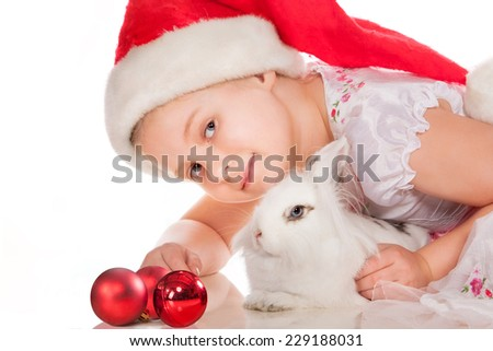 Happy girl in Santa hat with white rabbit on white background