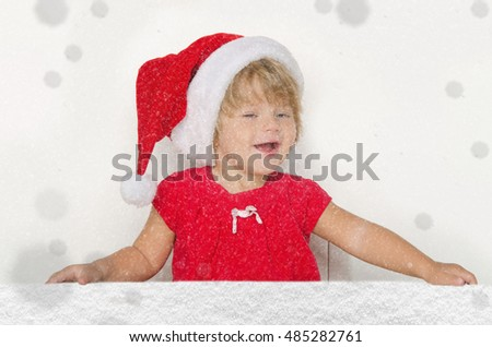Happy girl in Santa suit with snow studio shot