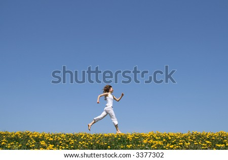 Happy girl in summer white clothes running in a flowering dandelion field. - stock photo
