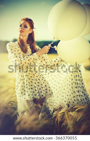 Happy girl in summerlight with white balloons - stock photo