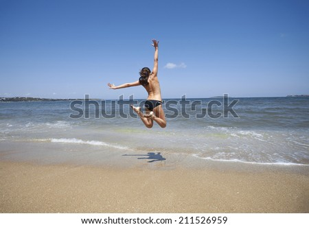 Happy girl in swimsuit jumping on the beach.