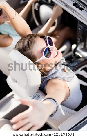 Happy girl in the car with her hands up. Having fun while driving the car - stock photo