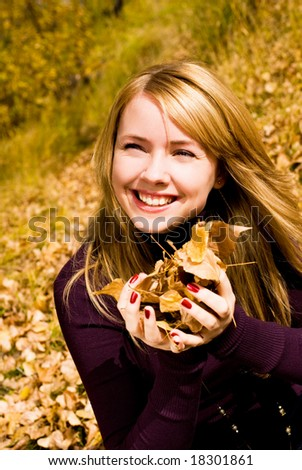 happy girl in the park with yellow leaves in her hands - stock photo