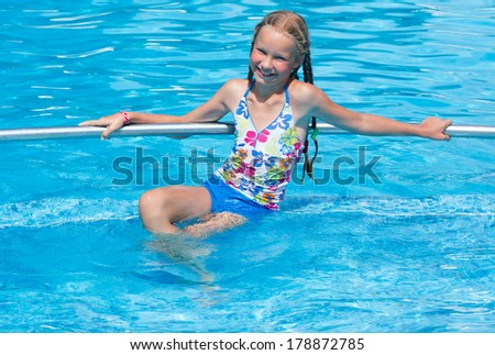 Happy girl in the summer outdoor pool.