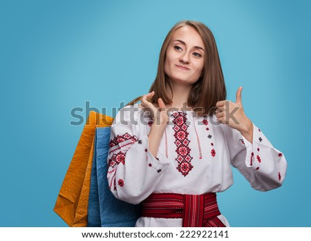 Happy girl in the Ukrainian national dress and shopping bags showing thumbs up - stock photo