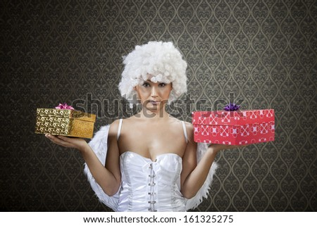 Happy girl in white angel costume with colorful gift boxes. - stock photo